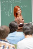 Student girl standing front of green chalkboard looking at classmates