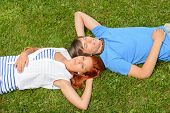 Teenage couple lying on grass relaxing closed eyes top view
