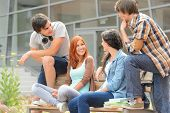 Group of student friends sitting bench outside college hanging out