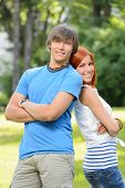 Teenage friends couple leaning against each other in sunny park