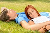 Teenage couple relaxing lying on grass closed eyes summer day