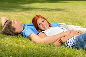 Teenage couple enjoying sun lying together on grass relaxing