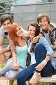 Cheerful group of high school friends hanging out outside campus