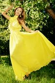 Romantic young woman in beautiful yellow dress on a green lawn in a blooming garden.
