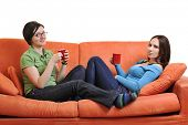 two young woman isolated on white with cup off coffee talking and chating isolated on whtie on orang
