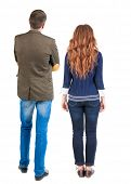 Back view of young couple hug and look into the distance. beautiful friendly girl and guy together.