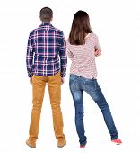Back view of young couple (man and woman) hug and look into the distance. beautiful friendly girl an