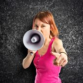 Redhead Girl Shouting With A Megaphone Over Black Background