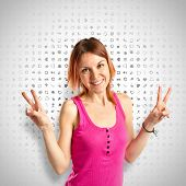 Young Woman Doing Victory Gesture Over Grey Background