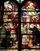 PARIS,FRANCE - NOV 11,2012:Saint Vincent de Paul raising a newborn and christening, stained glass.St Severin is Catholic church in the Latin Quarter. It is one of the oldest churches on the Left Bank.