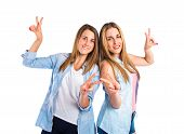 Girls Doing Victory Gesture Over White Background