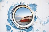 Ship Wreck Behind Round Porthole In White And Blue Wall