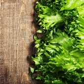 Fresh Green Salad Over Wooden Background - Healthy Or Vegetarian Food Concept. Lettuce Salad Backgro