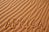 Word Africa writen on sand in the dunes of Erg Chebbi in the Sahara Desert, Morocco.
