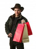 Young sexy man wearing winter clothes with copy space shopping bags isolated on white