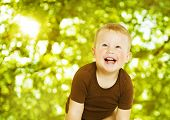 Happy Child Smiling Over Green Background. Close Up Baby Portrait.