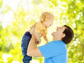 Father Child Happy Playing. Dad Raise Up Smiling Son Over Green Abstract Background
