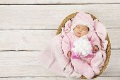 Baby Girl With Gift Sleeping On Wooden Background, Newborn In Basket With Present. Birthday Party