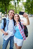 Happy young woman taking photo of herself and her boyfriend during journey