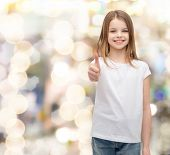 t-shirt design and happy people concept - smiling little girl in blank white t-shirt showing thumbs