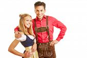Happy smiling couple in traditional bavarian outfit with dirndl dress and leather pants