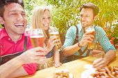 Happy friends laughing in beer garden in Bavaria in summer