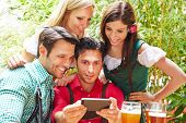 Happy friends taking selfie in bavarian beer garden in summer