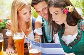 Friends looking together at drinks menu in beer garden in Bavaria