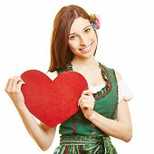 Smiling woman in dirndl dress holding red heart in Bavaria