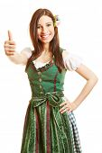 Smiling happy woman in green dirndl dress holding her thumbs up