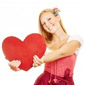 Happy woman in dirndl dress holding a big red heart
