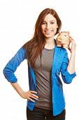 Happy young woman carrying a piggy bank on her shoulder