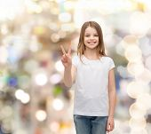 gesture and happy people concept - smiling little girl in white blank t-shirt showing peace gesture