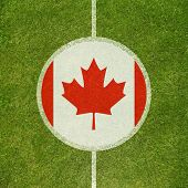 Football field center closeup with Canadian flag in circle