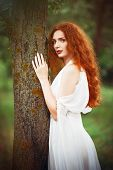 Beautiful Redhead Woman Wearing White Dress Stands Near Tree