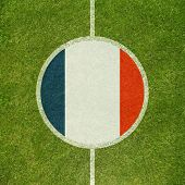 Football field center closeup with French flag in circle