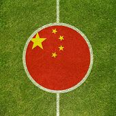 Football field center closeup with Chinese flag in circle