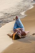 Beautiful woman in bikini top and jeans on the beach. Bali.
