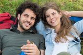 Young Happy Couple Resting On Grass Looking At Camera