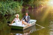 image of ponds  - beautiful young wedding couple blonde bride with flower and her groom just married on small boat at pond with evening sun - JPG