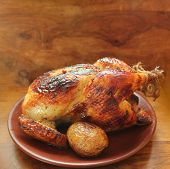 Grilled whole chicken on wooden background