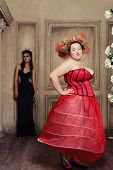 Two queens in carnaval dress. Black and red. Holiday picture.