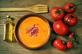 an earthenware bowl with spanish salmorejo, tomatoes and a bottle of olive oil on a rustic wooden ta