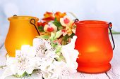 Bright icon-lamps with flowers on table on bright background