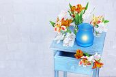 Bright icon-lamp with flowers on wooden stand on light background