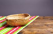 Empty wicker basket on wooden table, on dark background