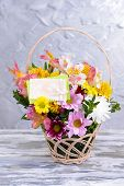 Beautiful bouquet of bright flowers in wicker basket on table on grey background