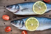Two Raw Seabass Fish With Lemon And Cherry Tomatoes On Wooden Background
