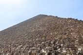 stock photo of the great pyramids  - View up the side of Great Pyramid of Giza in Cairo Egypt on baking hot day with the heat haze and sun blinding the image at the top - JPG