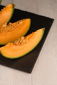 stock photo of honeydew melon  - Juicy honeydew melon on a black slate tray - JPG